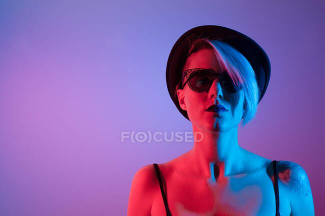Atractiva mujer con sombrero de disparar en el estudio con luces azules y rojas - foto de stock
