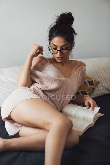 Чуттєва жінка брюнетка з книгою охолодження на ліжку — стокове фото