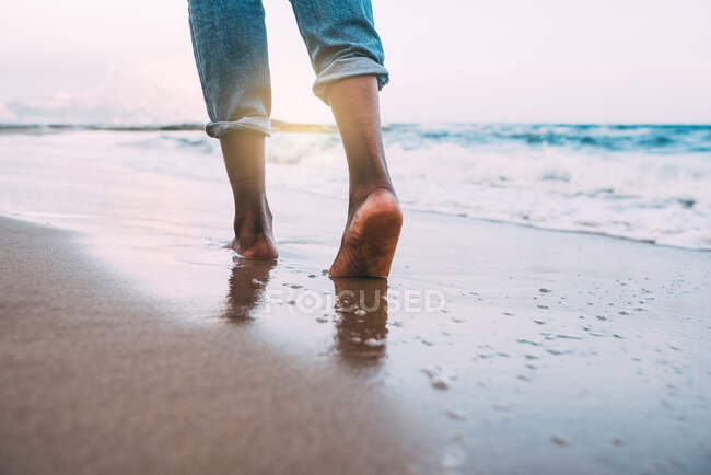 Woman walking on the beach barefoot — Stock Photo