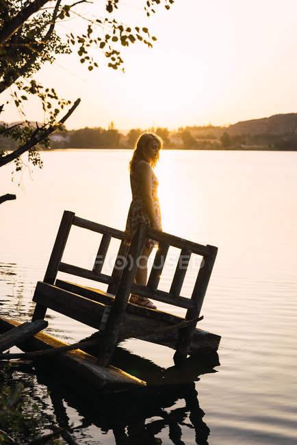 Dreamy woman standing on sunken pier in sunlight — Stock Photo