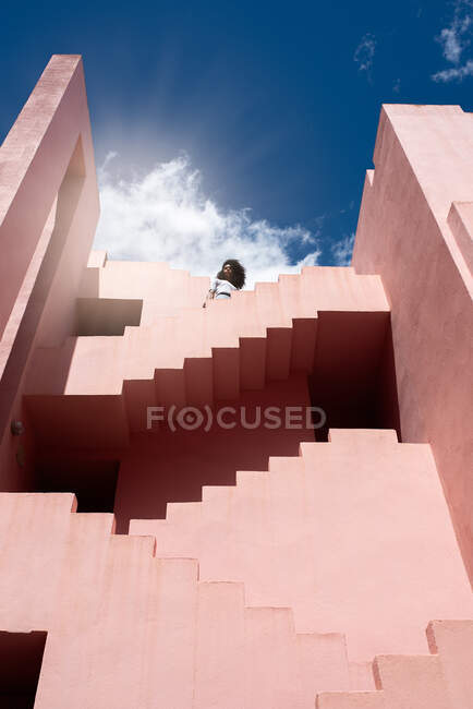 Black woman relaxing in a colorful geometric building stairs — Stock Photo