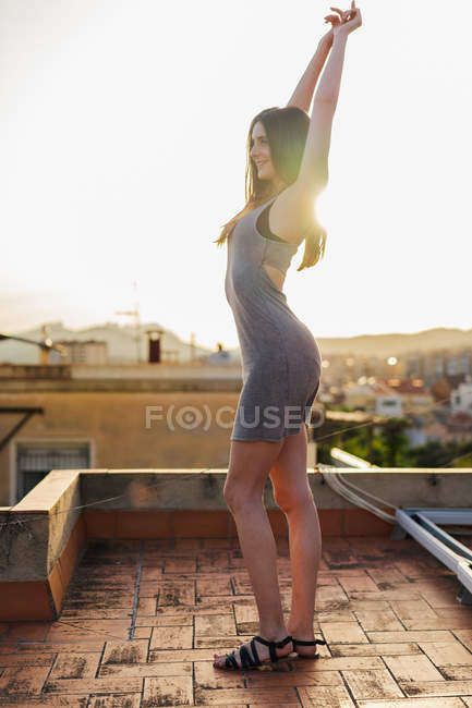 Brunette woman in summer dress standing on terrace on roof of old building at sunset — Stock Photo