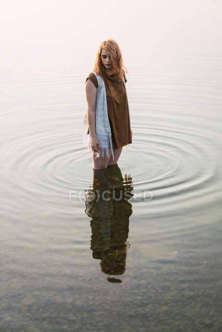 Donna in piedi in acque limpide del lago e guardando giù — Foto stock