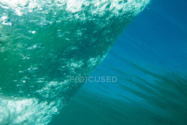 Underwater background of bright turquoise wave with white air bubbles rolling up on calm water surface in ocean — Stock Photo