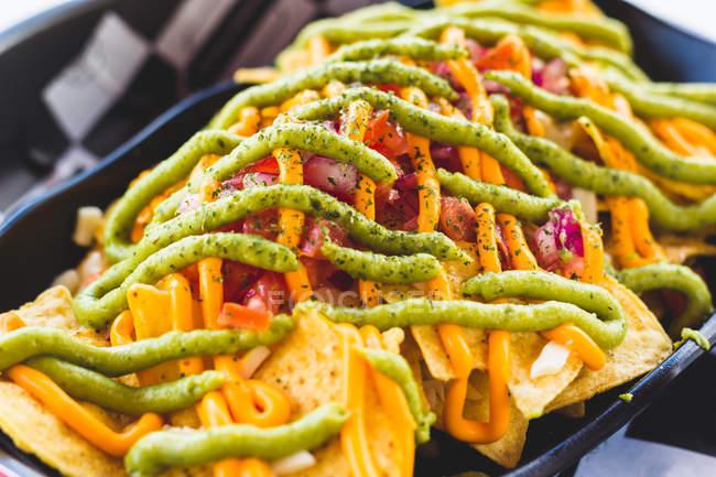 Gros plan des croustilles de maïs croustillant coulé avec différentes sauces et servis comme collation — Photo de stock