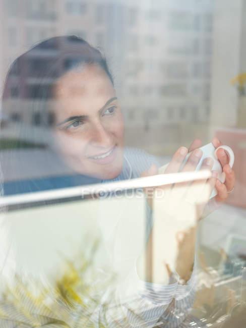 Jovem mulher de pé perto da janela — Fotografia de Stock