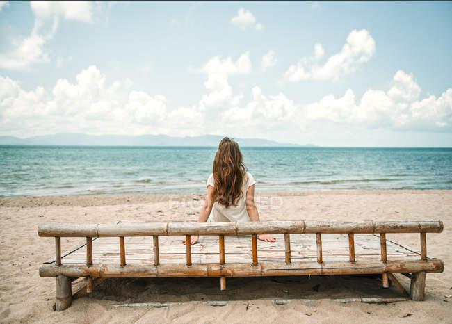 Задній вид жінка сидить на дереві і дивлячись на океану на пляжі — стокове фото