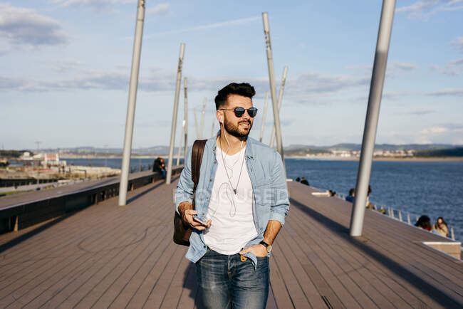 Trendy hipster strolling on waterfront — Stock Photo