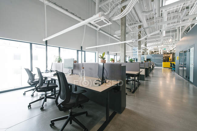 Inside shot of new open space office with colorful furniture on workplace and light from windows — Stock Photo