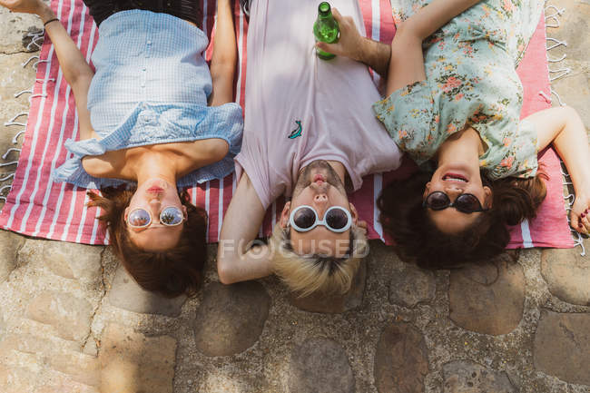 Young women and man in sunglasses and casual clothes grimacing while lying on blanket outdoors — Stock Photo