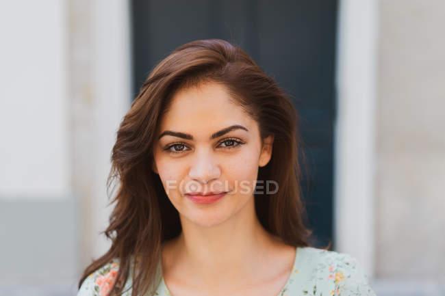Sorrindo jovem mulher olhando para a câmera na rua — Fotografia de Stock