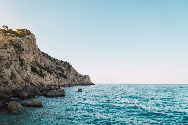 Panorama of clear blue sea water against rocky cliffs of shoreline and blue sky — Stock Photo