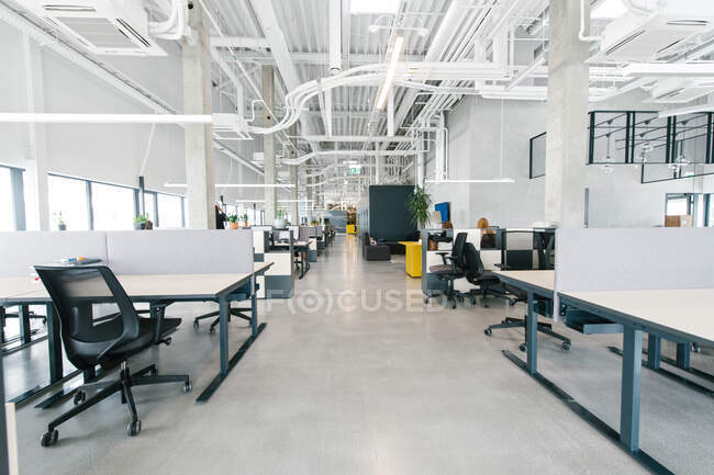 Interior shot of light white and black design of open space office with modern illumination — Stock Photo