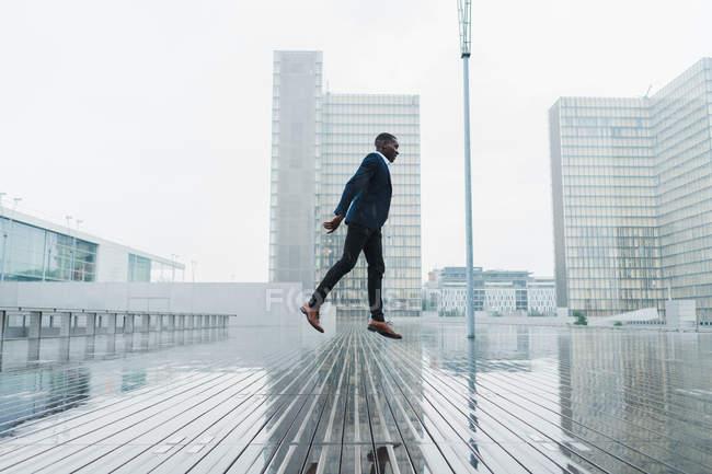 Homem étnico em roupas de negócios elegantes pulando no pavimento molhado com vidro da cidade e edifícios de concreto no fundo — Fotografia de Stock