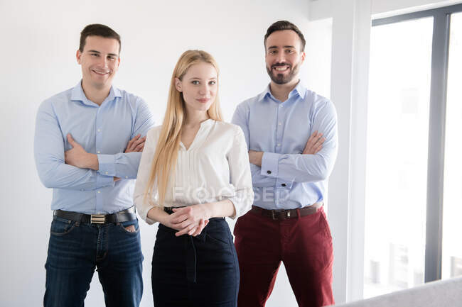 Group of office colleagues standing together relaxed with crossed arms and looking at camera smiling in spacious room at glass wall and door — Stock Photo