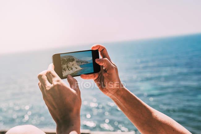 Mãos humanas tirando foto seascape com telefone celular — Fotografia de Stock