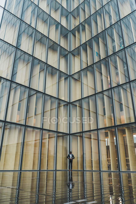 Businessman standing on pavement against modern glass building — Stock Photo