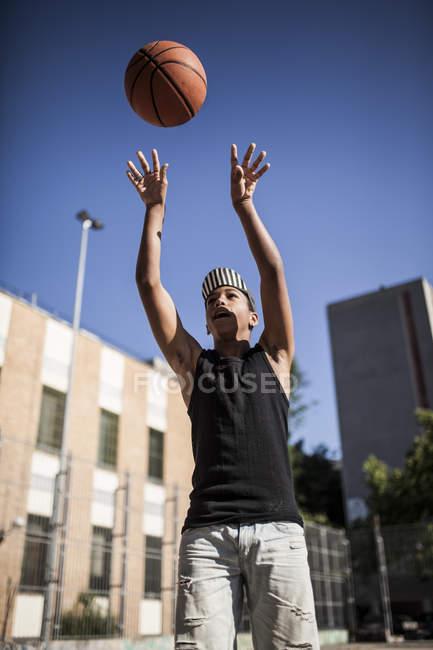 Мальчик в кепке играет в баскетбол на открытом воздухе — стоковое фото