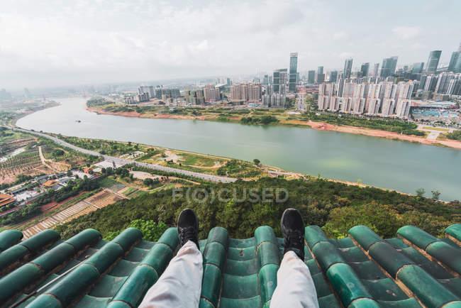 Piernas de turista en la azotea con paisaje de fondo, Nanning, China - foto de stock