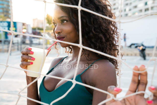 Alluring sensual black woman having drink with straw while standing behind volleyball net on beach — Stock Photo