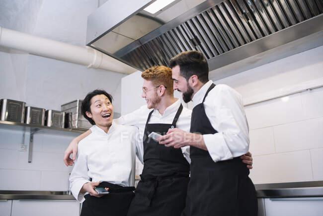 Три різні чоловіки в куховарській формі сміються і переглядають смартфони, стоячи на кухні ресторану разом — стокове фото
