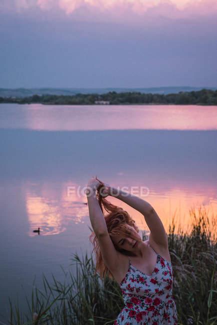 Mujer sensual en vestido de verano de pie en la orilla del lago al atardecer - foto de stock