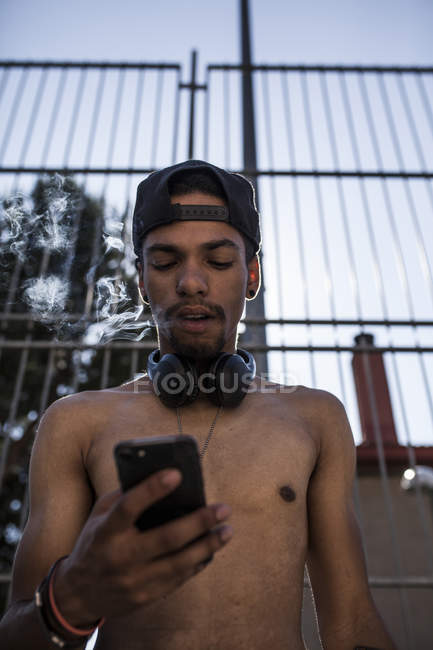 Afro young boy listening to music with headphones and smartphone while smoking in front of grating — Stock Photo