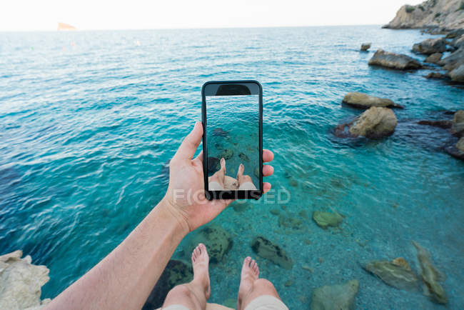 Hand of man using taking photo with smartphone of legs while sitting on cliff above turquoise water of sea — Stock Photo