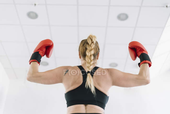 Back view of muscular woman in red boxing gloves showing biceps while standing on blurred background of gym — Stock Photo