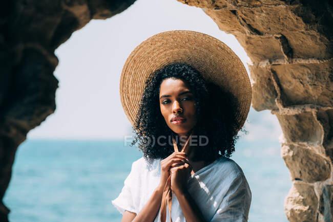 Mujer negra con sombrero de paja en ruinas antiguas junto al mar - foto de stock