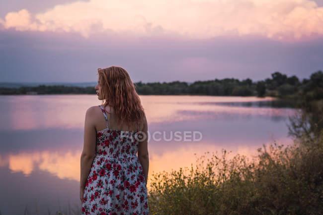 Романтическая женщина в летнем платье, стоящая на берегу озера на закате — стоковое фото