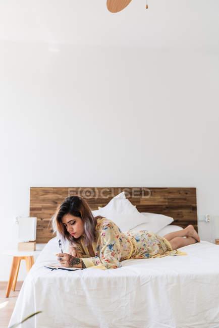Junge Frau im Seidenmantel auf dem Bett liegend und Skizzen im Notizblock im stilvollen Schlafzimmer — Stockfoto