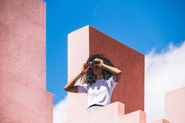 Black woman in a colorful geometric building looking throughout a field glass — Stock Photo