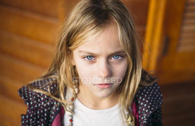 Portrait de fille blonde aux yeux bleus debout fond en bois — Photo de stock