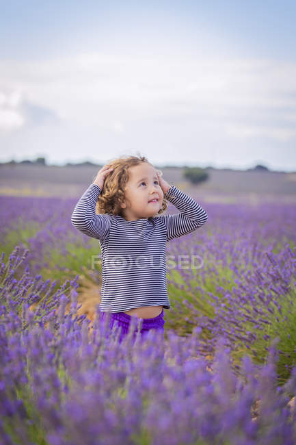 Little curly innocent girl standing in blooming lavender flowers and looking up — Stock Photo