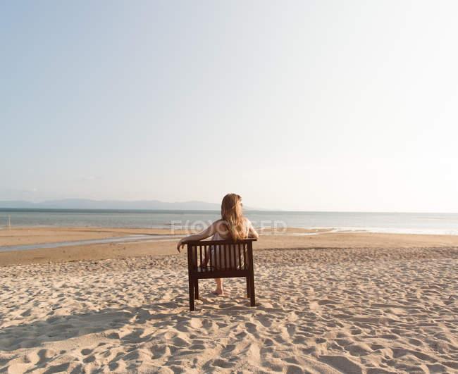 Вид сзади женщины, расслабляющейся на стуле на песчаном пляже и смотрящей на океан — стоковое фото
