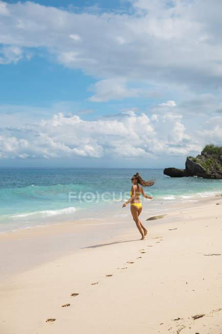 Donna felice emozionante in bikini giallo camminando sulla spiaggia di sabbia dell'oceano — Foto stock