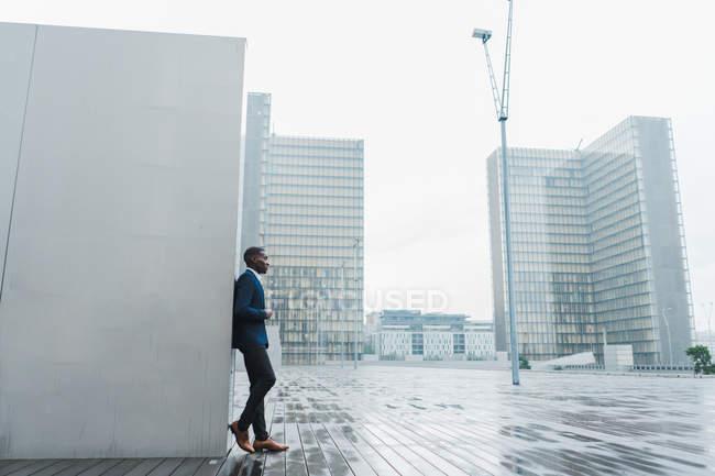 Афроамериканский бизнесмен опирается на стену на открытом воздухе с современными зданиями на заднем плане — стоковое фото
