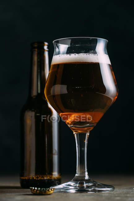 Бокал пива на темном фоне с бутылкой пива — стоковое фото