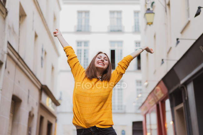 Smiling woman in yellow cardigan standing on street with hands up — Stock Photo