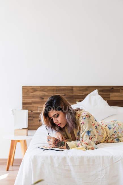 Mujer joven en bata de seda acostada en la cama y haciendo bocetos en bloc de notas en el elegante dormitorio - foto de stock