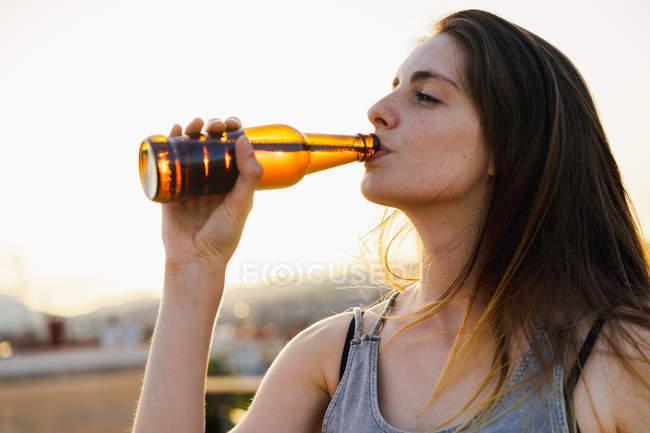 Счастливая молодая женщина пьет пиво из бутылки на открытом воздухе — стоковое фото