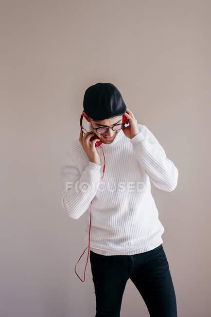Homem casual com fones de ouvido em pé no fundo cinza — Fotografia de Stock