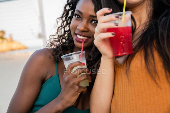 Smiling women enjoying drinks on beach — Stock Photo