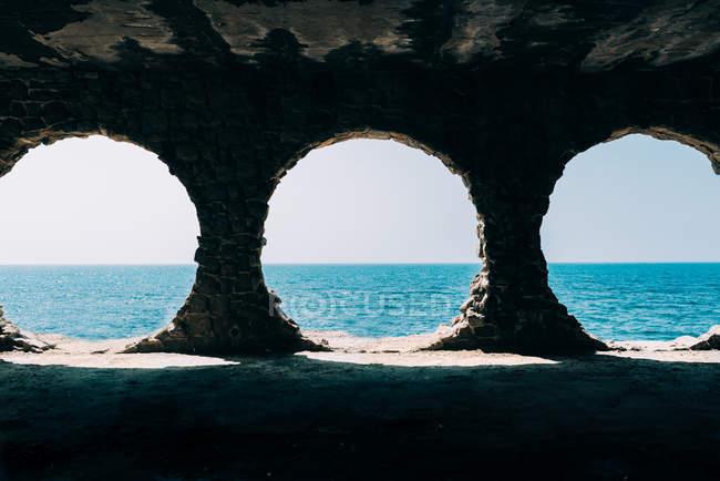 Blick auf das blaue Meer durch antike Ruinen mit Löchern — Stockfoto
