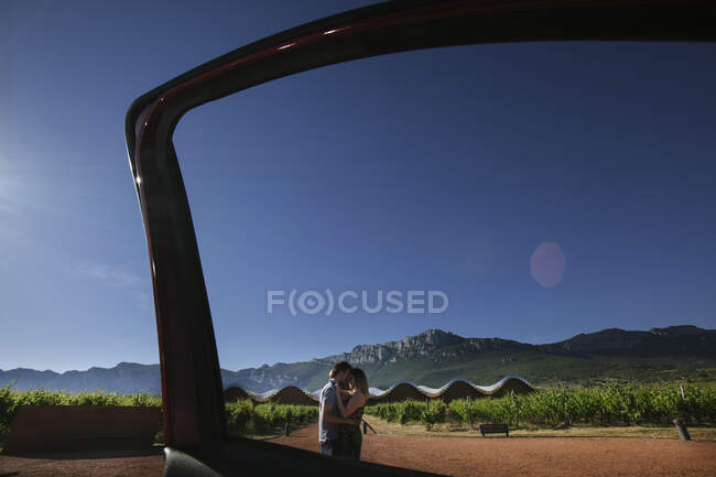 Side view of loving couple standing on road with green vineyard plantation on background with blue sky and mountains — Stock Photo