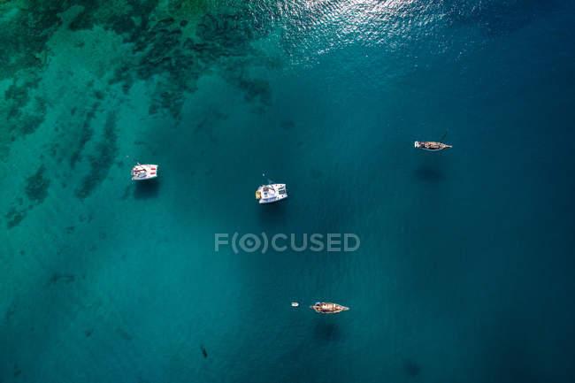Vue aérienne de bateaux colorés et radeaux voile dans l'eau de mer profonde sombre journée d'été ensoleillée, La Graciosa, îles Canaries — Photo de stock