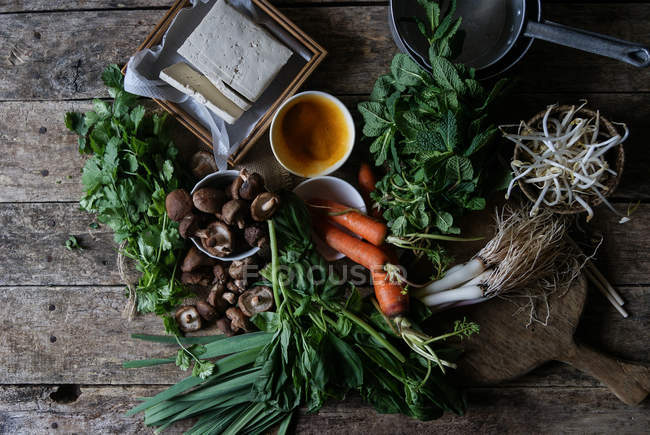 Verduras arregladas en mesa rústica para preparar crepe tradicional Banh Xeo - foto de stock