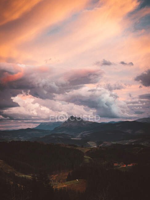 Picturesque landscape of valley with mountains and evergreen woods under colorful sunset sky, Bizkaia — Stock Photo