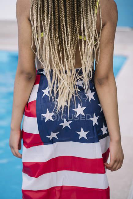 Женщина с афроволосами, завернутая в американский флаг, стоящая в бассейне — стоковое фото